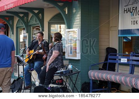 HARBOR SPRINGS, MICHIGAN / UNITED STATES - AUGUST 4, 2016: Musicians perform in front of The Outfitter Sporting Goods Store at the Street Musique event in downtown Harbor Springs.