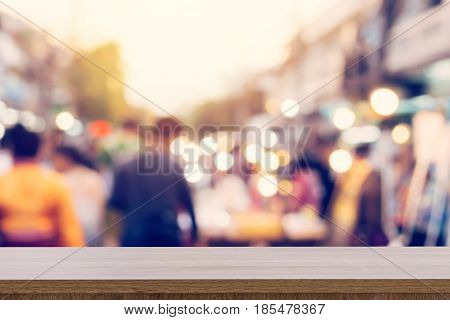 Wood Table And Display Montage With Blurred People Walking Through A City Street. Vintage Toned Phot