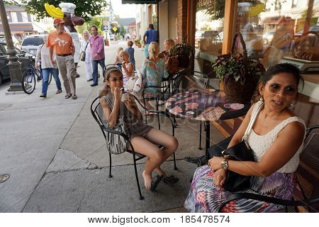HARBOR SPRINGS, MICHIGAN / UNITED STATES - AUGUST 4, 2016: A girl enjoys eating Kilwin's ice cream, at a table outside store's front window, during the Street Musique event on Main Street in downtown Harbor Springs.