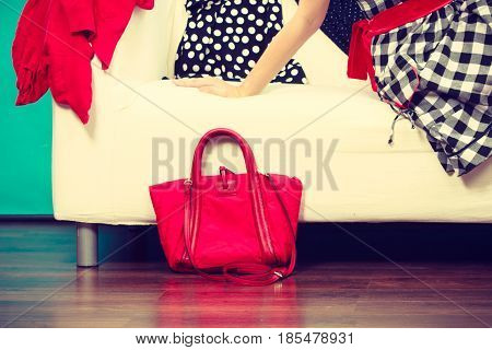Woman Resting On Sofa Next To Red Bag