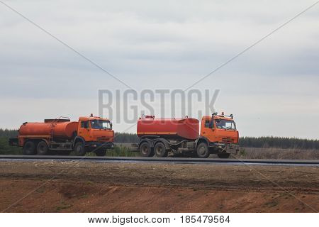 Road construction work - two red watering trucks at highway among field, telephoto