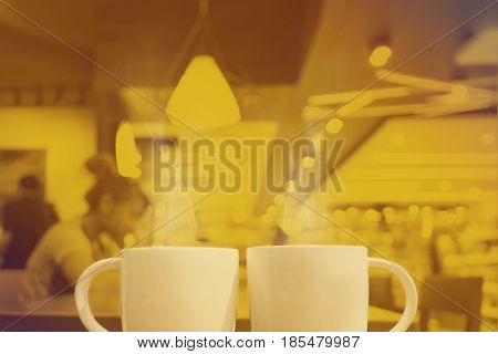 Yellow Duotone of two cup of coffee at cafe background Mock up for adding your text.