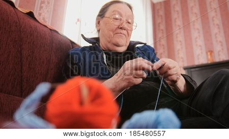 Woman pensioner home - lady knits wool socks sitting on the sofa - hobby, bottom view