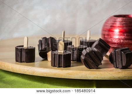 Magnificent portioned chocolate desserts on comfortable wooden sticks. Professional baking. Wooden polished round tray. White background