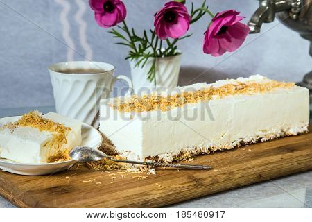 Delightful cheesecake with crumbled kadaif. On a saucer with a spoon lies a piece of cake. The background is cup with tea and vase with flowers. Professional bakery