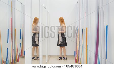 Girl in clothing store chooses dress near mirror in fitting room - shopping concept, middle shot