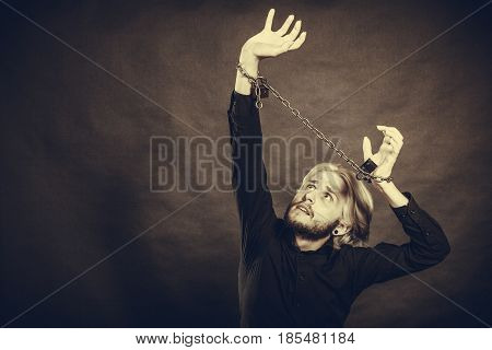 No freedom social problems concept. Sad man with chained hands studio shot on dark grunge background
