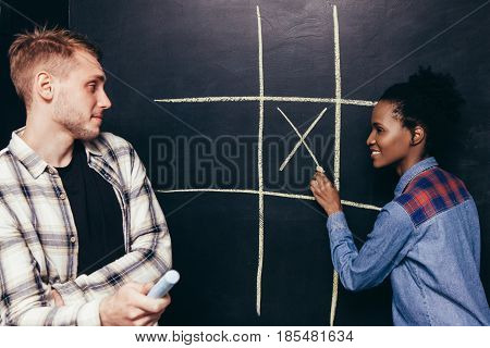Interracial happy couple, white man and black woman play tic tac toe game. Fun leisure, great entertainment, joy and happiness, battle of the sexes concept.