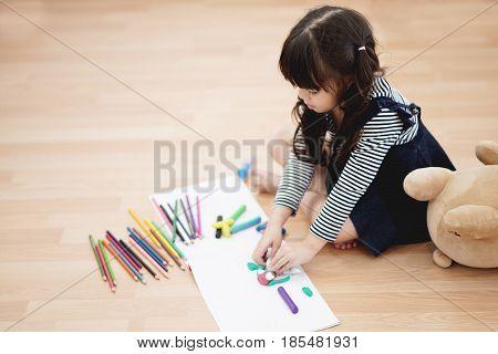 Portrait of beautiful kid having art activity on the floor selective focused.