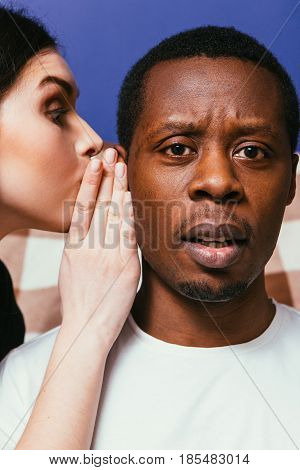 Gossip white woman whispering on ear to black man, closeup. Girl unable to keep important secret. Tattle and hearsay concept