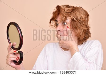 Shocked and surprised middle aged woman looking at her skin and unkempt hair in the mirror