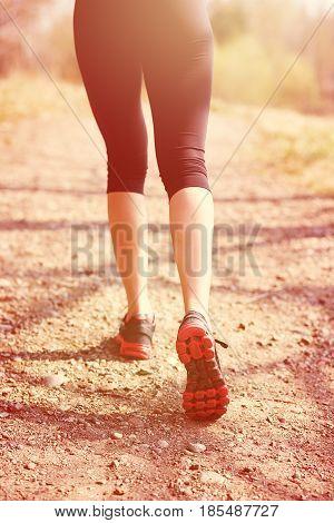 Runner feet running on road closeup on shoe. woman, fitness sunrise jog workout welness concept.