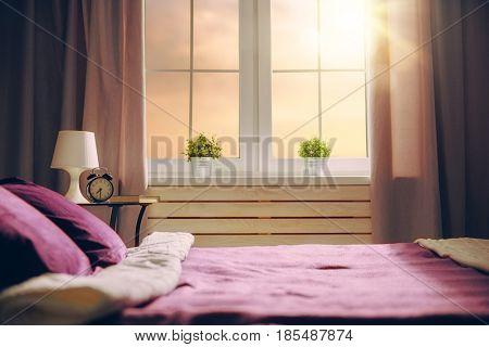 Bedroom in purple colors. Big comfortable double bed in elegant classic room.