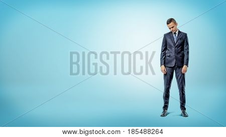 A depressed businessman standing with shoulders slumped on blue background. Losing your fortune. Getting fired. Bad news.