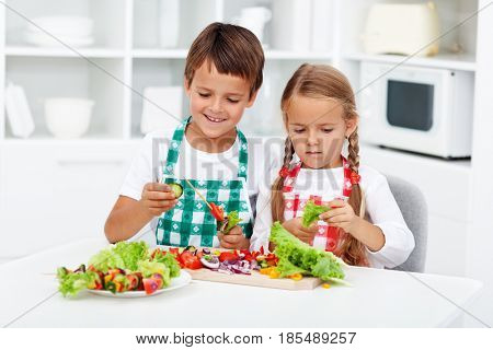 Young kids preparing vegetables on a stick for a healthy snack - taking their job seriously