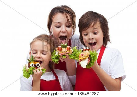 Kids and woman taking a bite of funny creatures sandwiches - isolated