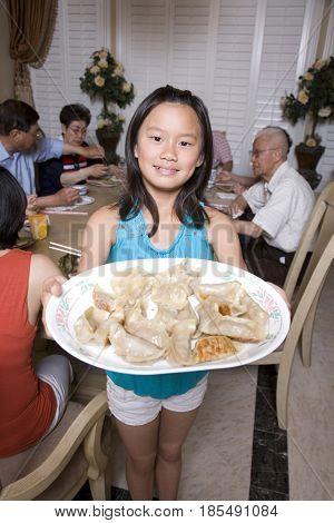 Chinese girl serving family dumplings