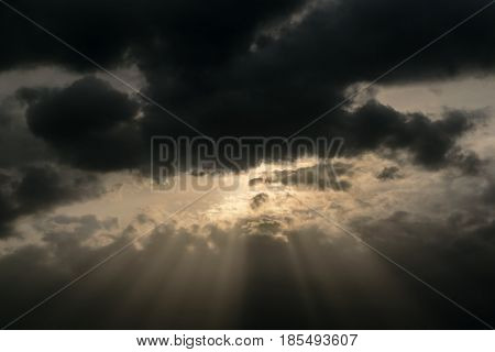 In the evening sky through the rain clouds the sun peeps out. From the sun the sun's rays diverge. The rays illuminate thunderclouds. Threatened atmosphere.
