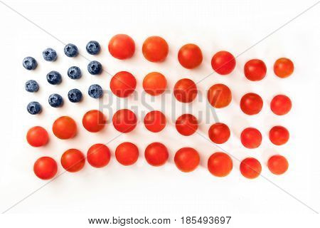 A photo of a representation of the American flag, made up by blueberries and cherry tomatoes on a white background. A culinary Independence Day greeting card, 4th of July banner