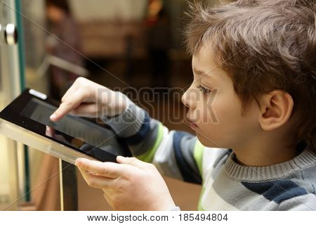 Boy using touch screen in a museum