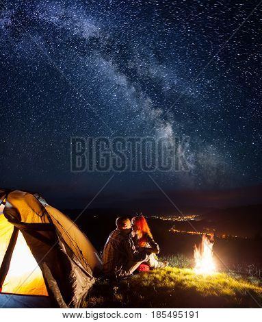 Night Camping. Loving Couple Backpackers Sitting And Kissing Near A Campfire And Tent Under The Star