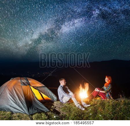 Night Tent Camping. Happy Couple Tourists Sitting By Campfire Under Incredibly Beautiful Starry Sky