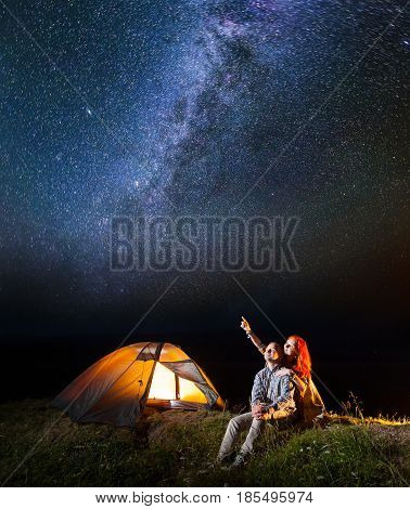 Tourist Couple - Girl And Guy Looking At The Shines Starry Sky At Night. Pair Sitting Near Camping