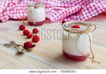 Two yogurt jars with fruit on the bottom on wooden background. Homemade yoghurt with raspberry jam. Rustic style. Concept for heathy eating lifestyle or breakfast.