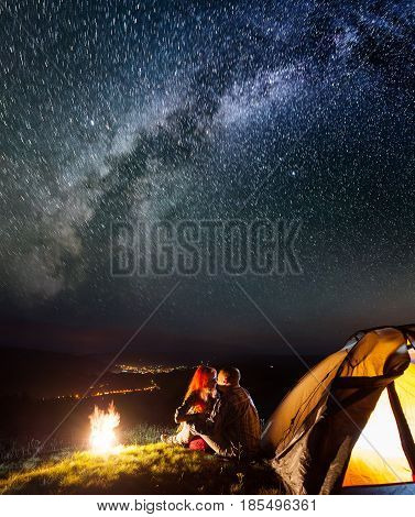 Night Camping. Romantic Couple Hikers Sitting And Kissing Near A Campfire And Tent Under The Stars A