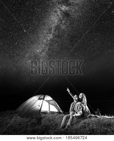 Tourist Couple - Girl And Guy Looking At The Shines Starry Sky At Night. Pair Sitting Near Camping.