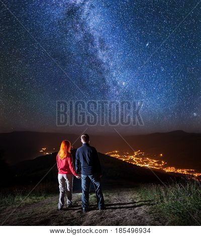 Back View Of Charming Couple Holding Hands, Standing On A Hill And Enjoying Incredibly Beautiful Sta