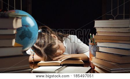 Eight years bored school girl , table place with books and globe, education concept