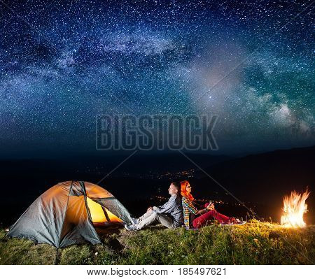 Romantic Couple Sitting By Bonfire Near Glowing Tent Under Incredibly Beautiful Starry Sky. On The B