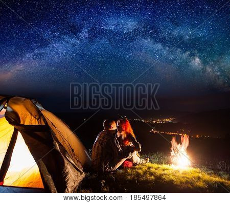 Night Camping. Charming Pair Tourists Sitting And Kissing Near A Campfire And Tent Under The Stars.