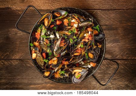 A full skillet of marinara mussels, shot from above on a dark rustic background with a place for text