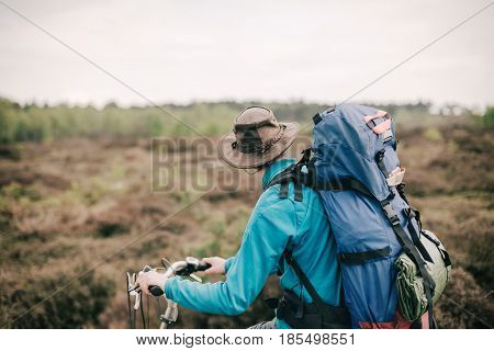 Traveler With Hat And Backpack On Bicycle Looking Over Moorland.