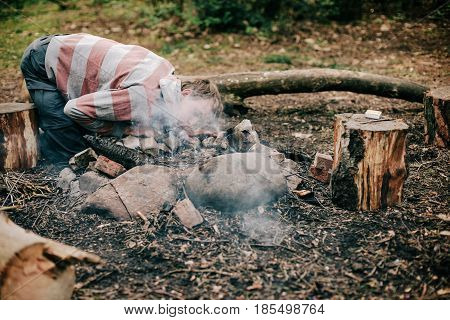 Camper Blowing Into Campfire To Get Fire Started.