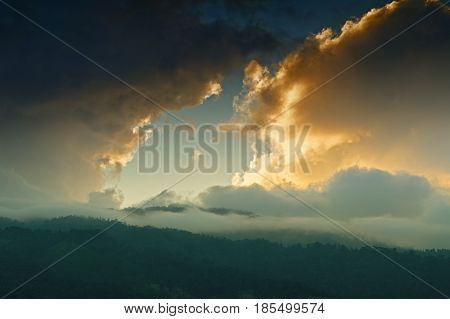 Light coming through window of clouds from setting sun over Himalayan Mountain peaks. Dramatic cloud formation with sunset colours over Indian Mountain peaks.
