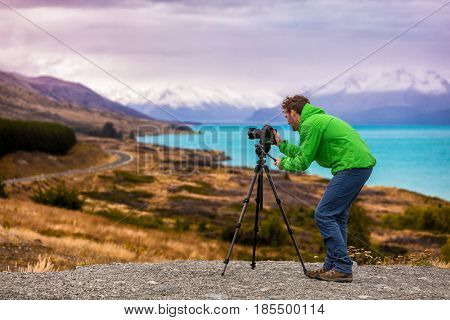 Travel photographer taking nature landscape pictures in New Zealand at sunset. Peters Lookout, Road to Mount Cook by Lake Pukaki.