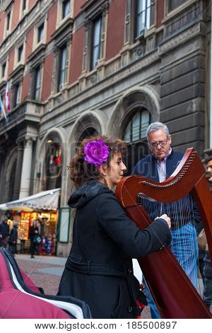 MILAN ITALY - FEBRUARY 26: Classical musician harpist playing instrument in the street on february 26 2017