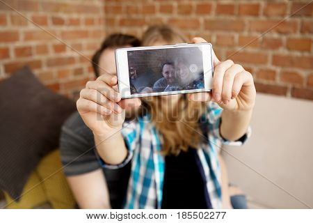Two young people making photo by smartphone, in home.