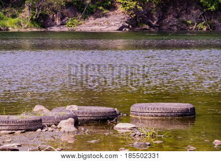 Four old tires lineup next to each other to form a foot bridge at the bank of a river in South Korea