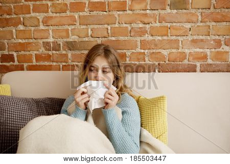 Young ill woman sitting on sofa, she is having cold or flu.