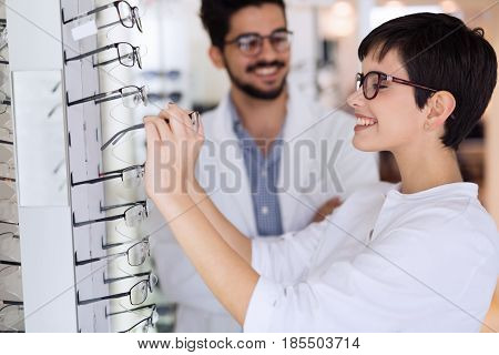 Beautiful woman with optician trying eyeglasses at optics store