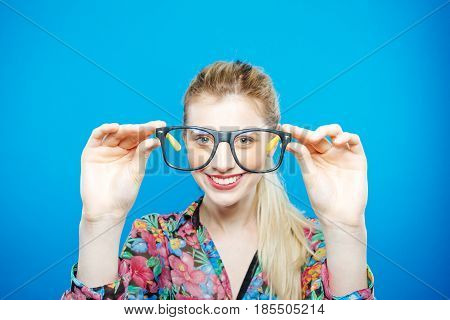 Portrait of Funny Blonde Woman with Ponytail in Colorful Shirt and Fashionable Eyeglasses on Blue Background. Sensual Cute Girl is Posing in Studio.