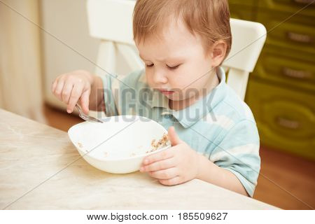 Little boy eats porridge. Healthy food concept