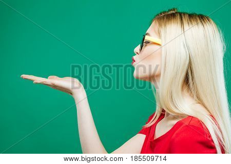 Side View of Young Woman with Blond Hair, Eyeglasses and Red Top Holding Empty Space on Her Hand and Kissing on Green Background in Studio.