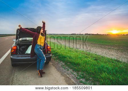 woman stratching near car on sunrise long car trip