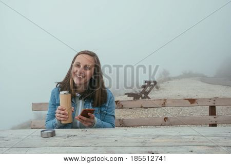 Young Woman With Phone  Sitting On Wooden Bench And Drinking Hot Tea From A Thermos In Autumn Forest