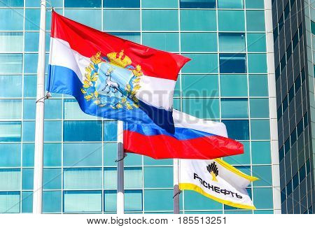 Samara Russia - May 7 2017: Flags of Samara region Russia and oil company Rosneft fluttering against the office building of the OJSC Samaraneftegaz
